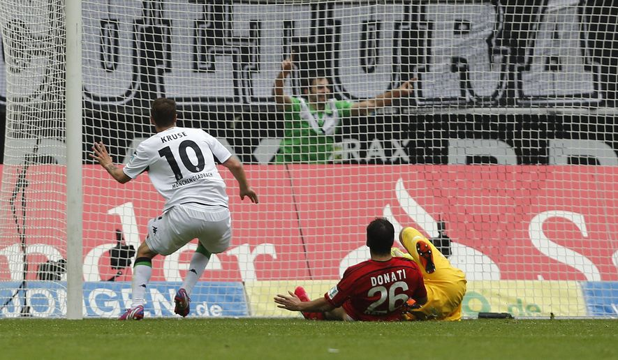 Moenchengladbach's Max Kruse, left, scores during the German first division Bundesliga soccer match between Borussia Moenchengladbach and Bayer Leverkusen in Moenchengladbach, Germany, Saturday, May 9, 2015. (AP Photo/Frank Augstein)