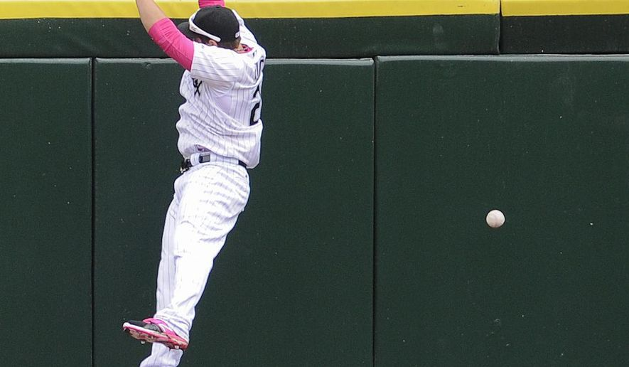 Chicago White Sox left fielder J.B. Shuck tries to catch an RBI-triple hit by Cincinnati Reds' Devin Mesoraco  during the fourth inning of a baseball game in Chicago on Sunday, May 10, 2015. (AP Photo/Matt Marton)