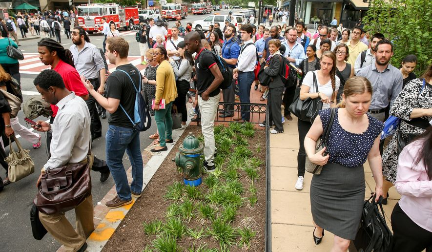 Washington Metro passengers move towards buses outside the Foggy Bottom Metro Station in Washington, Monday, May 11, 2015, to take them to Rosslyn, Va., after D.C. Fire and EMS officers say a Metro third rail insulator was damaged, shutting down metro service between Foggy Bottom and Rosslyn. (AP Photo/Andrew Harnik)