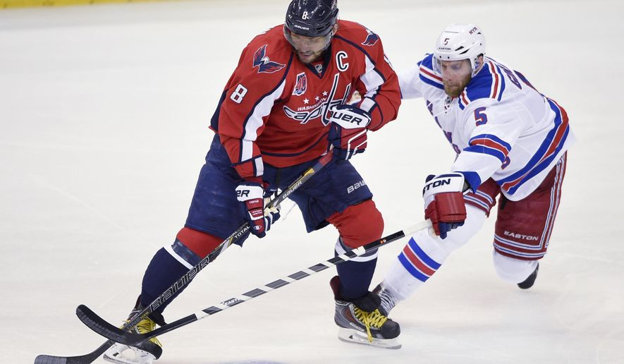 New York Rangers defenseman Dan Girardi (5) battles for the puck against Washington Capitals left wing Alex Ovechkin (8), from Russia, during the first period of Game 6 in the second round of the NHL Stanley Cup hockey playoffs, Sunday, May 10, 2015, in Washington. (AP Photo/Nick Wass)