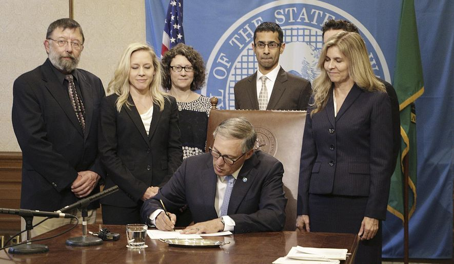 Gov. Jay Inslee, seated, signs a DNA preservation bill surrounded by supporters, including the bill's sponsor, Rep. Tina Orwall, right, Monday, May 11, 2015, in Olympia, Wash. The new law requires DNA collected in any felony case charged as a violent or sex offense to be preserved through the length of the offender's sentence, including post-prison community custody. (AP Photo/Rachel La Corte)