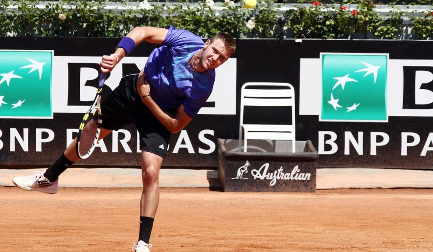Jack Sock from US serves the ball to France's Gilles Simon during their match at the Italian Open tennis tournament, in Rome, Monday, May 11, 2015. (AP Photo/Felice Calabro')