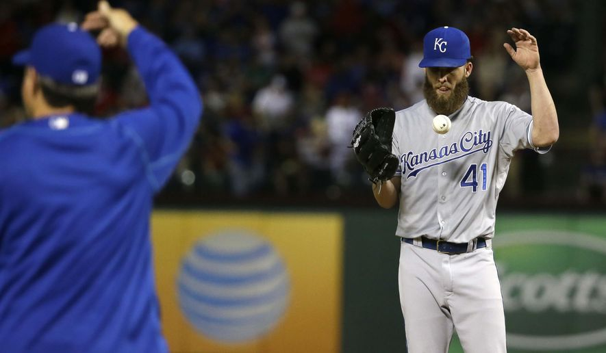 Kansas City Royals starting pitcher Danny Duffy (41) tosses the ball as manager Ned Yost, left, walks to the mound to put in a new pitcher during the fourth inning of a baseball game against the Texas Rangers in Arlington, Texas, Monday, May 11, 2015. (AP Photo/LM Otero)
