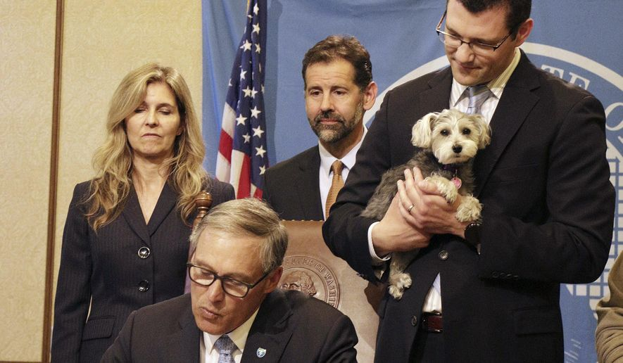 Gov. Jay Inslee signs into law a measure that  makes it a civil offense to lock an animal in a car or enclosed space in dangerous conditions, like extreme heat or cold, May 11, 2015, in Olympia, Wash. He was joined by the bill's sponsor, Sen. Joe Fain, right, who brought his dog, Waffles, to the signing. (AP Photo/Rachel La Corte)