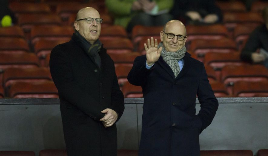 FILE - In this Wednesday, Feb. 11, 2015 file photo, Manchester United board members Avi Glazer, left, and Joel Glazer wait for play to begin before the English Premier League soccer match between Manchester United and Burnley at Old Trafford Stadium, Manchester, England. The 10th anniversary of Manchester United's purchase by American investors will pass on Tuesday, May 12, 2015 without champagne corks popping at the club or fan protests on the streets. The mood in the boardroom is one of relief: European football riches figure to flow into Old Trafford once again in 2015-16 after this season's absence from the Champions League. (AP Photo/Jon Super, File)