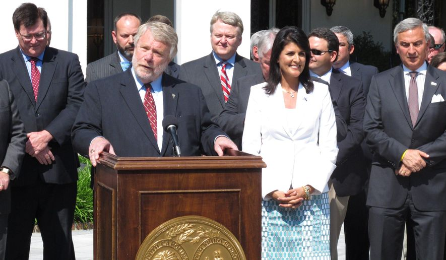 South Carolina Commerce Secretary Bobby Hitt, at podium, talks about Volvo Car Corp.'s announcement it will build its first plant in North America in Berkeley County as Gov. Nikki Haley, second right, listens on Monday, May 11 2015, in Columbia, S.C. South Carolina beat out four other states for the $500 million plant that will employ 4,500 workers. (AP Photo/Jeffrey Collins)