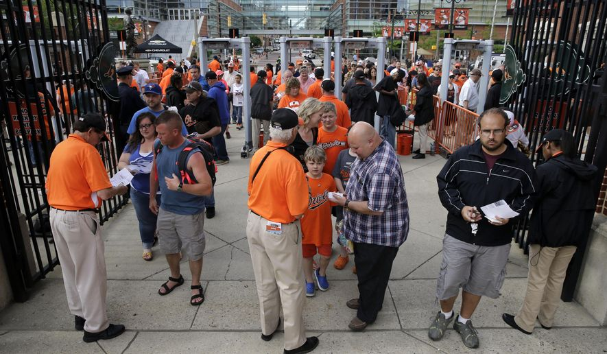 Ushers check fans' tickets as they enter Orioles Park at Camden Yards before a baseball game between the Baltimore Orioles and the Toronto Blue Jays, Monday, May 11, 2015, in Baltimore. Playing in front of their home fans for the first time in two weeks, the struggling Orioles hope a game at Camden Yards can serve as a pick-me-up for themselves and the beleaguered city. (AP Photo/Patrick Semansky)