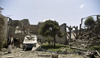 A man loyal to former Yemeni president Ali Abdullah Saleh inspects at Saleh's house destroyed by a Saudi-led airstrike in Sanaa, Yemen, Sunday, May 10, 2015. Yemen's Shiite rebels and their allies in the country's splintered armed forces said Sunday they would accept a five-day humanitarian cease-fire to allow aid to reach civilians after more than a month of daily Saudi-led airstrikes. Saleh and his forces back Shiite rebels also known as the Houthis, who are also backed by Iran. (AP Photo/Hani Mohammed)