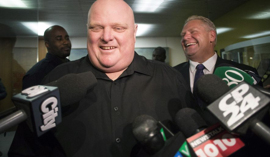 FILE - In this Nov. 21, 2014, file photo, Toronto's outgoing Mayor Rob Ford, front center, stands next to his brother Doug Ford outside his office as he speaks with the media before signing bobblehead dolls in his likeness in Toronto. Doctors have removed a cancerous tumor from the former Toronto mayor's abdomen and he has regained consciousness after an intensive surgery that kept him under anesthesia for about 10 hours, his chief of staff said late Monday, May 11, 2015. (AP Photo/The Canadian Press, Chris Young, File)