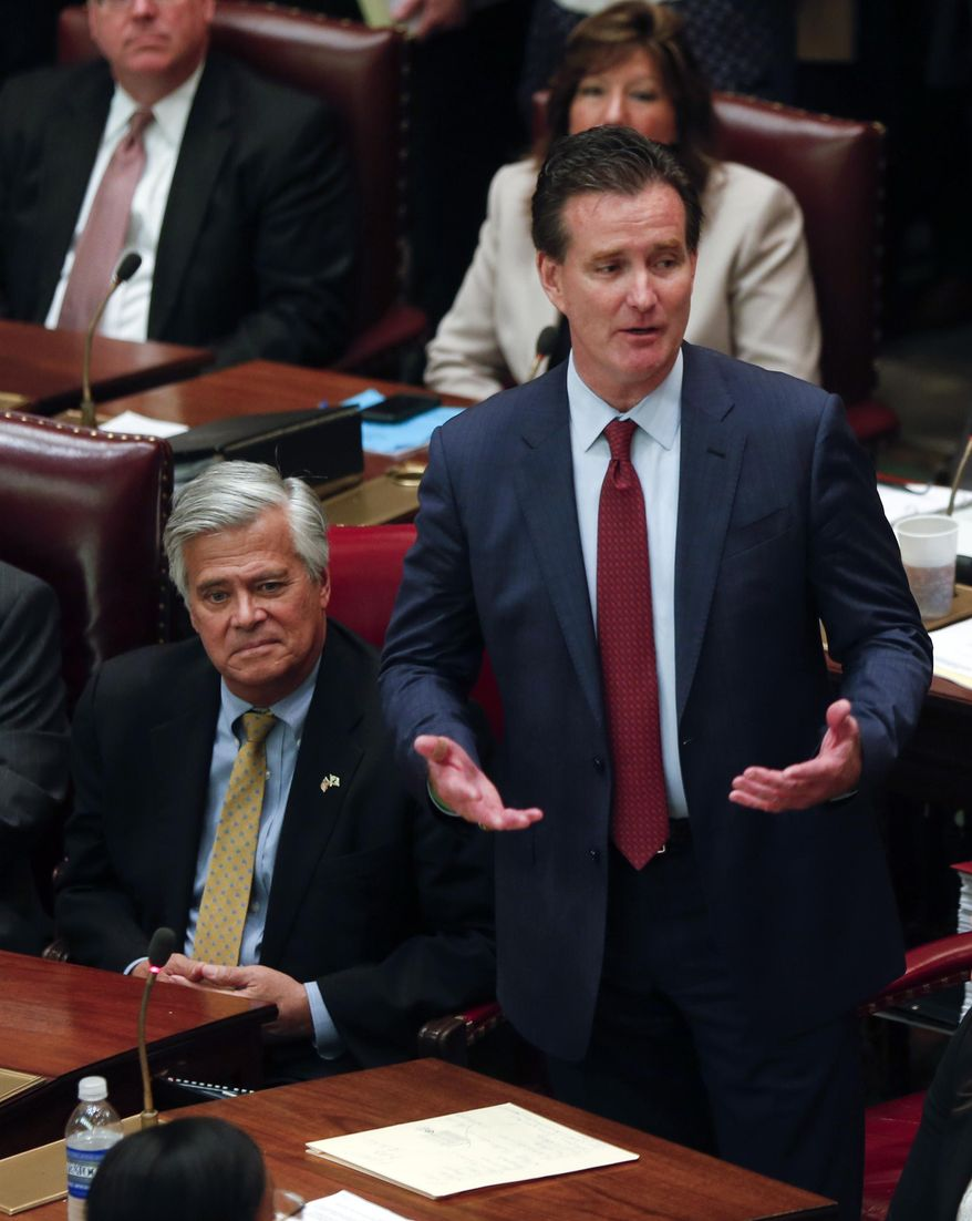 New Senate Majority Leader John Flanagan, R-Smithtown, speaks in the Senate Chamber at the Capitol on Monday, May 11, 2015, in Albany, N.Y. Flanagan replaces Republican Dean Skelos, left, who resigned his position as leader following his arrest on federal corruption charges. (AP Photo/Mike Groll)