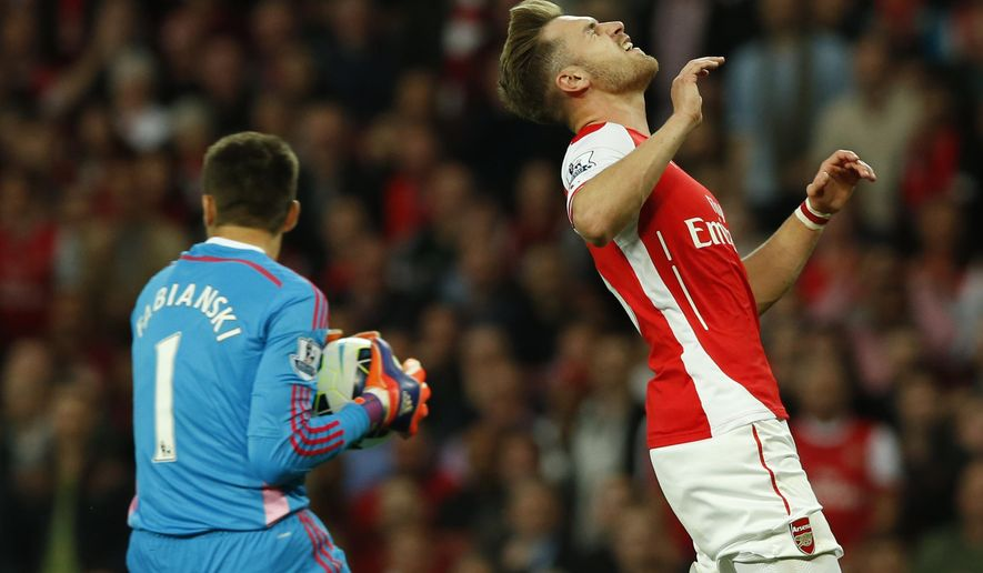 Arsenal's Aaron Ramsey, right, misses a chance to score a goal during their English Premier League soccer match between Arsenal and Swansea City at the Emirates stadium in London, Monday May 11, 2015. (AP Photo/Alastair Grant)