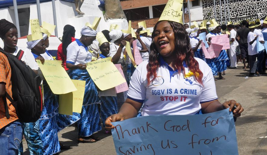 A woman holds a placard as she and others celebrate Liberia being an Ebola free nation in Monrovia, Liberia, Monday, May 11, 2015. Liberians are gathering in the streets of the capital to celebrate the end of the Ebola epidemic in this West African country. Monday's festivities come after the World Health Organization declared over the weekend that Liberia was finally Ebola-free. (AP Photo/ Abbas Dulleh)