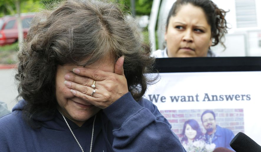 Marilyn Covarrubias, left, the mother of Daniel Covarrubias, covers her face while talking to reporters Monday, May 11, 2015, outside police headquarters in Lakewood, Wash. The interim police chief in Lakewood says officers shot and killed Daniel Covarrubias in a lumber yard last month because he pointed a cell phone at them as though it were a gun. At right is Lanna Covarrubias, sister of Daniel Covarrubias. (AP Photo/Ted S. Warren)