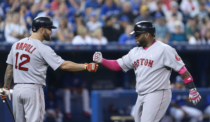Boston Red Sox first baseman Mike Napoli (12), left, celebrates with Boston Red Sox third baseman Pablo Sandoval (48) after Sandoval hit a two-run homer in the 5th inning of the baseball game between the Toronto Blue Jays and Boston in Toronto on Sunday, May 10, 2015. (Peter Power/The Canadian Press via AP) MANDATORY CREDIT