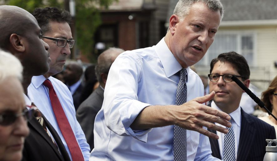 New York Mayor Bill de Blasio, second right, answers questions at a news conference at the Corona Family Residence, a homeless facility, in the Queens borough of New York, Monday, May 11, 2015. Mayor de Blasio is accompanied by Dept. of Homeless Services Commissioner Gilbert Taylor, second left, New York City Fire Commissioner Daniel A. Nigro, third left, and Dept. of Investigation Commissioner Mark Peters, right.  (AP Photo/Richard Drew)