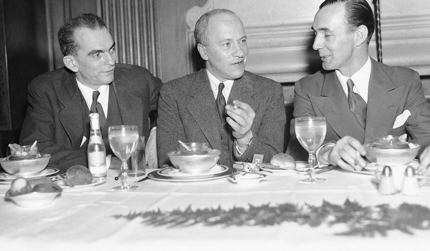 Walter Duranty, New York Times correspondent, center, at a luncheon given in his honor by the Association of Foreign Press Correspondents at the Hotel Lombardy in New York, April 16, 1936.  At left is Kenneth Durant, representative of TASS, Soviet news agency, and at right is A. Bernard Moloney, of Reuters, president of the association. (AP Photo/John Rooney)