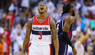 Washington Wizards Bradley Beal (3) reacts to hitting a three pointer over Atlanta Hawks DeMarre Carroll (5)  in the second half of the Eastern Conference Semifinals basketball game 4 on Monday, May 11, 2015, at the Verizon Center in Washington.  The Hawks won 106-101.   (Curtis Compton/Atlanta Journal-Constitution via AP)  MARIETTA DAILY OUT; GWINNETT DAILY POST OUT; LOCAL TELEVISION OUT; WXIA-TV OUT; WGCL-TV OUT