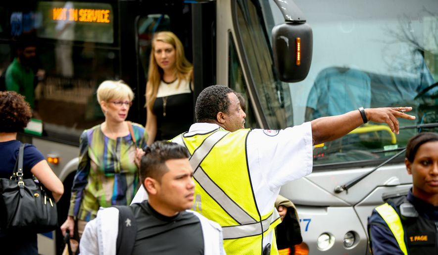 A Washington Metro employee directs Metro passengers arriving by bus from Rosslyn, Va. towards the Foggy Bottom Metro Station in Washington, Monday, May 11, 2015, after D.C. Fire and EMS officers say a Metro third rail insulator was damaged, shutting down metro service between Foggy Bottom and Rosslyn. (AP Photo/Andrew Harnik)