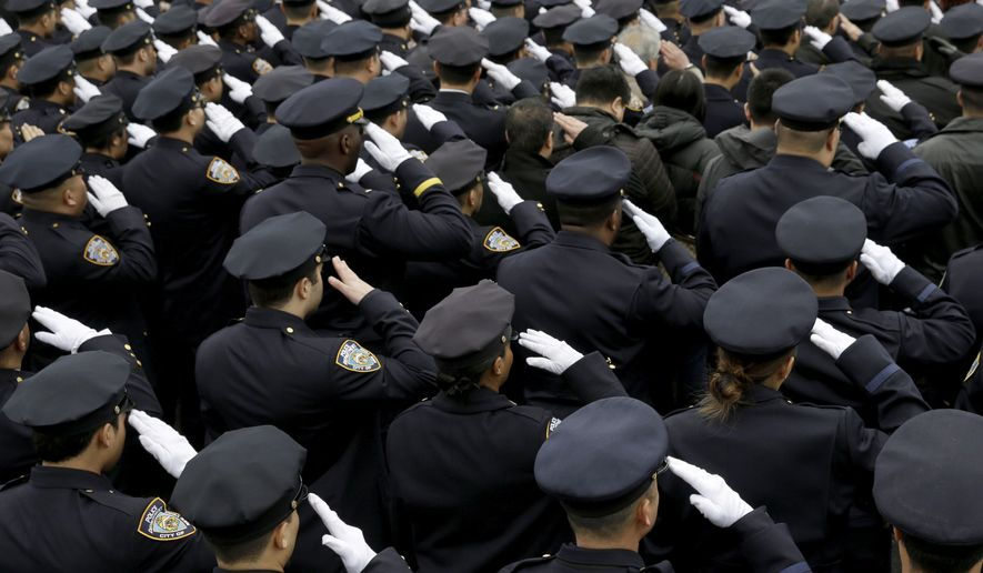 Police officer salute during the funeral of Officer Wenjian Liu in the Brooklyn borough of New York on Jan. 4. Liu and his partner, officer Rafael Ramos, were killed Dec. 20 as they sat in their patrol car on a Brooklyn street. The shooter, Ismaaiyl Brinsley, later killed himself. (Associated Press)
