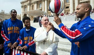 In this Wednesday, May 6, 2015, photo Harlem Globetrotters' Hi-Lite Bruton, second from left, Ant Atitkson, third from left,  look at teammate Flight Time Lang, right, helping Pope Francis spin the ball on his finger as they meet during the general audience in St. Peter's Square at the Vatican. (L'Osservatore Romano/Pool Photo via AP) **FILE**