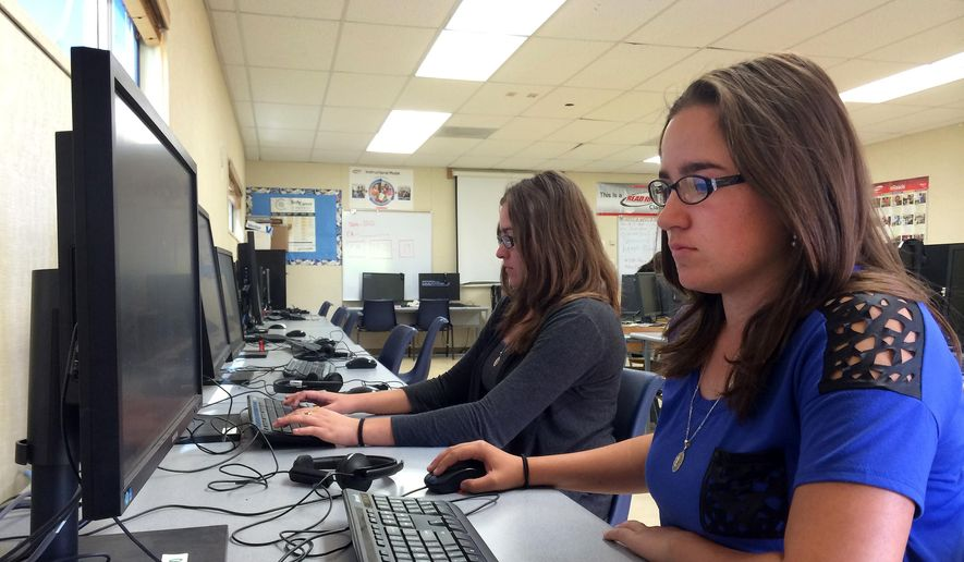 In this April 30, 2015, photo, Leticia Fonseca, 16, left, and her twin sister, Sylvia Fonseca, right, work in the computer lab at Cuyama Valley High School after taking the new Common Core-aligned standardized tests in New Cuyama, Calif. (AP Photo/Christine Armario)