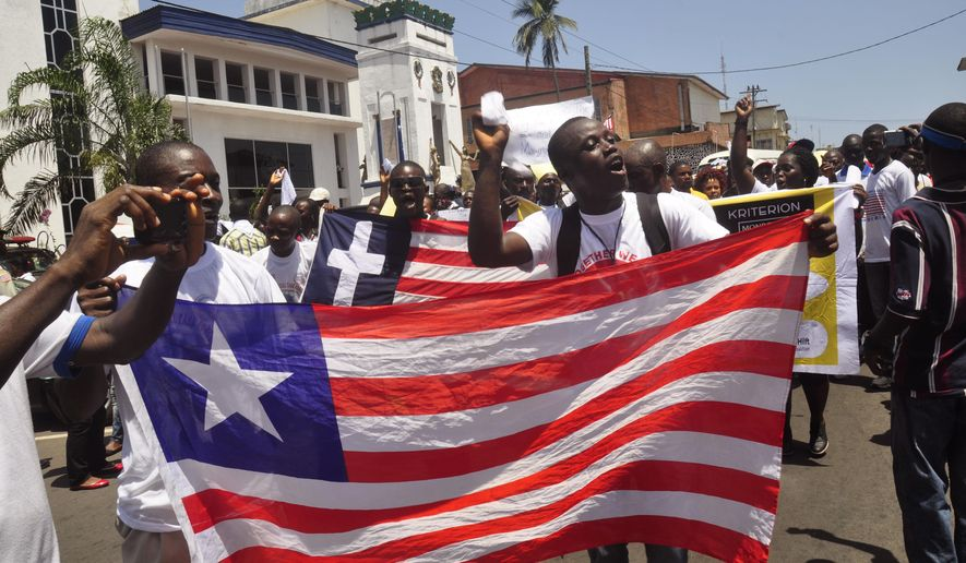 People display a representation of the Liberian flag as they celebrate Liberia being an Ebola free nation in Monrovia, Liberia, Monday, May 11, 2015. Liberians are gathering in the streets of the capital to celebrate the end of the Ebola epidemic in this West African country. Monday's festivities come after the World Health Organization declared over the weekend that Liberia was finally Ebola-free. (AP Photo/ Abbas Dulleh)