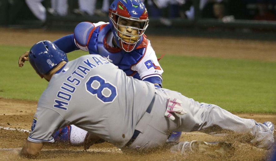 Kansas City Royals Mike Moustakas (8) is tagged out at home plate by Texas Rangers catcher Robinson Chirinos during the fourth inning of a baseball game in Arlington, Texas, Monday, May 11, 2015. Moustakas was attempting to score on a single by Royals designated hitter Kendrys Morales. (AP Photo/LM Otero)