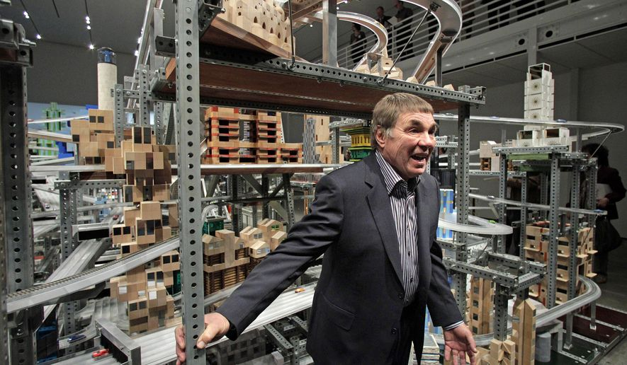 "FILE - In this Jan. 11, 2012 file photo, pop artist Chris Burden poses for photos in front of his kinetic sculpture, ""Metropolis II,"" at the Los Angeles County Museum of Art (LACMA) in Los Angeles. The colorful display of roads, cars, trains and buildings is art imitating what the artist foresees life being like in five or 10 years. Burden, the noted performance artist and sculptor who created a landmark piece at the Los Angeles County Museum of Art using antique city street lamps, has died. He was 69. His friend, Paul Schimmel, tells the L.A. Times that Burden died Sunday, May 10, 2015 from melanoma at his home in Topanga Canyon. He made complex installations, some with thousands of pieces, and works that had automated functions. Other works are in museums in New York, London and around the world.(AP Photo/Jae C. Hong, File)"