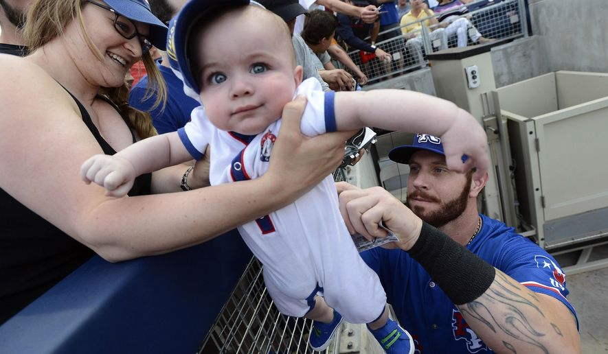 Texas Rangers' Josh Hamilton signs his autograph on the of back 6-month-old Drew Hooker as his mother Melissa holds him before a baseball game against the Nashville Sounds, Monday, May 11, 2015, in Nashville, Tenn. Hamilton is playing for the Round Rock Express AAA minor league baseball team before rejoining the Rangers after a rehab stint. (AP Photo/Mark Zaleski)