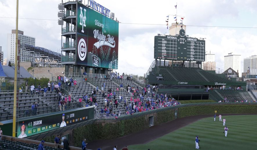 Chicago Cubs' fans watches batting practice from the left field bleachers before a baseball game between the Cubs and the New York Mets Monday, May 11, 2015, in Chicago. The Cubs opened the famous left field bleachers for the first time this season after major renovations.(AP Photo/Charles Rex Arbogast)