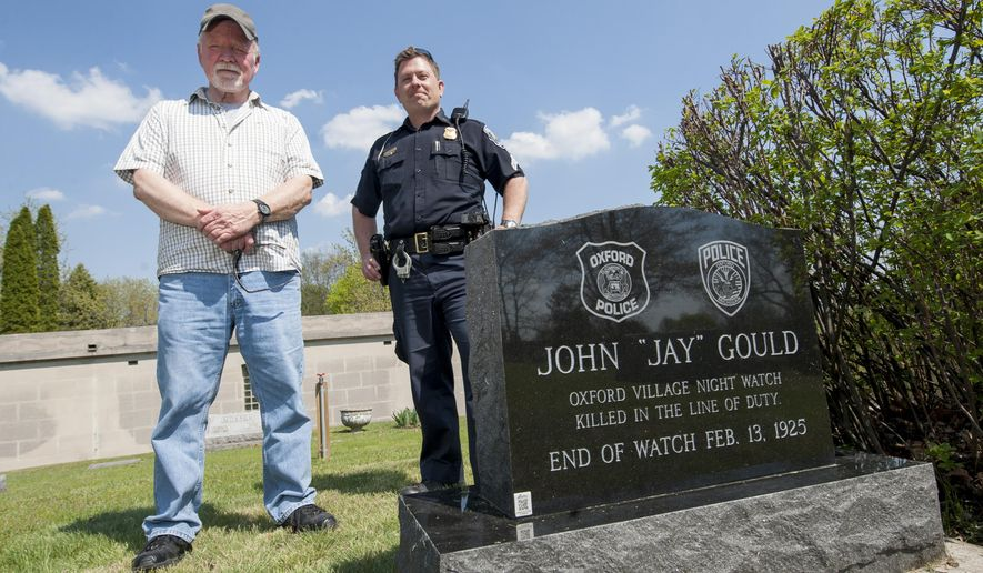 """Retired Captain James Malcolm, left, and Oxford police sergeant Mike Solwold, stand over the grave of former Oxford policeman John """"Jay"""" Gould at the Oxford Twp. Cemetery, on May 7, 2015.  Gould was killed in the line of duty in 1925 but was never given a headstone for his grave until Malcolm and Solwold raised the money for it recently.  (David Guralnick/ The Detroit News via AP)"""