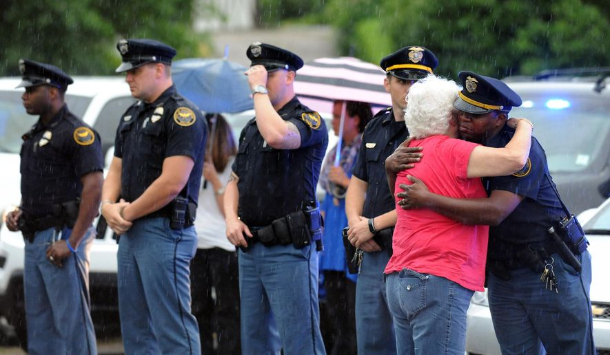 A woman hugs an officer during the procession for the body of Hattiesburg Police Officer Benjamin Deen, Monday, May 11, 2015, in Hattiesburg, Miss. Marvin Banks faces two counts of capital murder in the Saturday shootings of Officers Deen and Liquori Tate following a traffic stop. (Eli Baylis/The Hattiesburg American via AP)  NO SALES