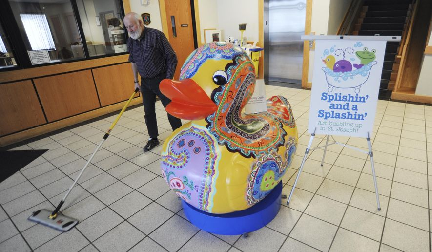 "City of St. Joseph employee Art Pearce sweeps up around the newest art sculpture on display at City Hall in St. Joseph, Mich., Thursday, Feb. 5, 2015. The piece ""Paisley Duck,"" by artist Betsy Kerr Reif, is part of this summer's public art display titled ""Splishin' and a Splashin,"" on display May 15-September 24, 2015, throughout the downtown area. (AP Photo/The Herald-Palladium, Don Campbell)"