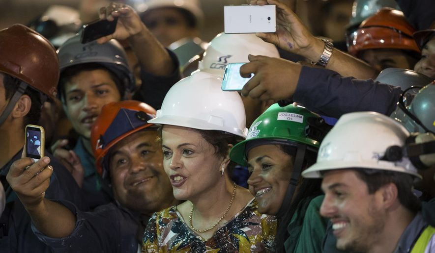 Brazil's President Dilma Rousseff poses for photos with subway construction workers as she visits the site of a new line being built in the Barra da Tijuca neighborhood of Rio de Janeiro, Brazil, Tuesday, May 12, 2015. (AP Photo/Felipe Dana)