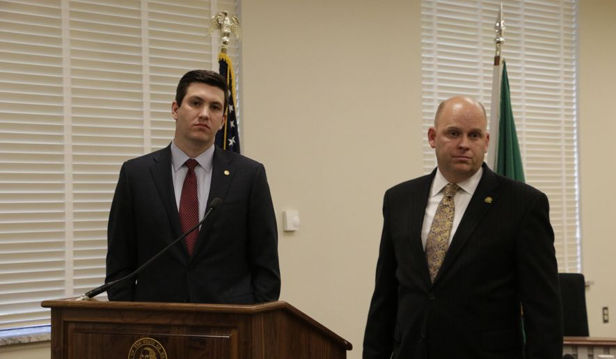 Reps. Drew Stokesbary, left, and Rep. Drew MacEwen, listen to a question at a press conference about their resolution seeking to impeach state Auditor Troy Kelley, Tuesday, May 12, 2015, in Olympia, Wash. Kelley is currently on unpaid leave after pleading not guilty in federal court to 10 felony counts, including allegations that he failed to pay taxes. (AP Photo/Rachel La Corte)