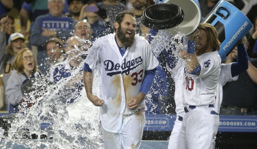Los Angeles Dodgers' Justin Turner, right, dumps water on Scott Van Slyke as they celebrate a three-run walk off home run by Van Slyke in a baseball game against the Miami Marlins, Monday, May 11, 2015, in Los Angeles. The Dodgers won 5-3. (AP Photo/Jae C. Hong)