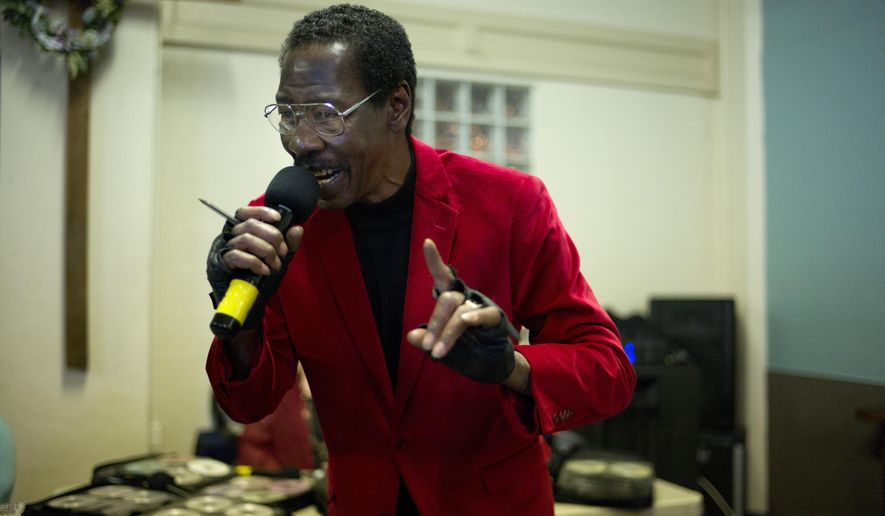 In this Wednesday, Feb. 4, 2015 photo, sporting a red velvet jacket, 63-year-old Skid Row resident Vincent Washington sings a song at karaoke night at the Central City Community Church of the Nazarene on Skid Row in Los Angeles. As people harmonize on Beatles songs, they begin to lock out the ugliness outside, where a misdirected look can launch a knife fight in a second. Where across 50 square blocks on the edge of City Hall and other landmarks that represent the rich and powerful the streets reek with the smell of urine. Where some 1,700 people bed down on filthy sidewalks every night. (AP Photo/Jae C. Hong)