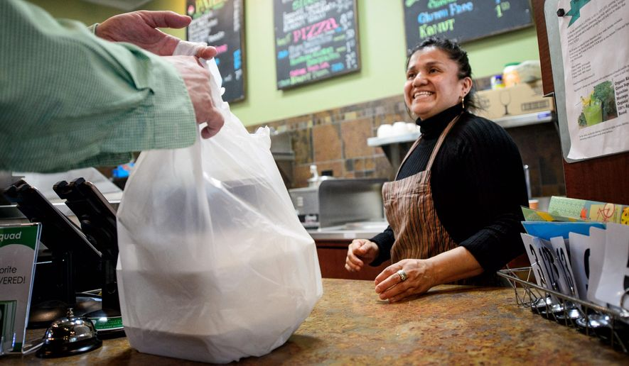 Sandra Mejia hands a carry-out food order to a customer at Vitali's Bistro on Monday, May 11, 2015 in St. Louis Park, Minn. (Glen Stubbe/Star Tribune via AP)  MANDATORY CREDIT; ST. PAUL PIONEER PRESS OUT; MAGS OUT; TWIN CITIES LOCAL TELEVISION OUT