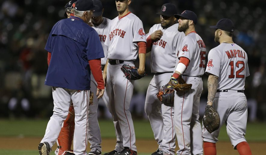 Boston Red Sox pitching coach Carl Willis, left, meets pitcher Rick Porcello in the sixth inning of a baseball game against the Oakland Athletics Monday, May 11, 2015, in Oakland, Calif. (AP Photo/Ben Margot)