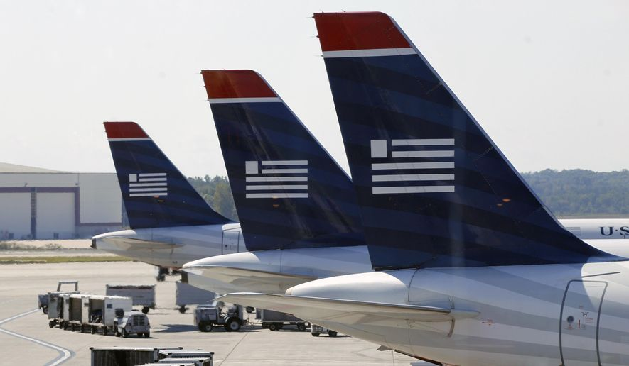 In this Thursday, Sept. 27, 2012, file photo, US Airways jets are parked at their gates at the Charlotte/Douglas International airport in Charlotte, N.C. (AP Photo/Chuck Burton, File)