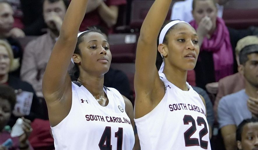 FILE- In this Jan. 29, 2015, file photo, South Carolina's A'ja Wilson, right, and Alaina Coates react to a 3-point shot by teammate Tina Roy, not shown, during the second half of an NCAA college basketball game against Alabama in Columbia, S.C. South Carolina's scoring duo expect their new roles of moving into the starting lineup should send the Gamecocks toward a second Final Four.  (AP Photo/Richard Shiro, File)