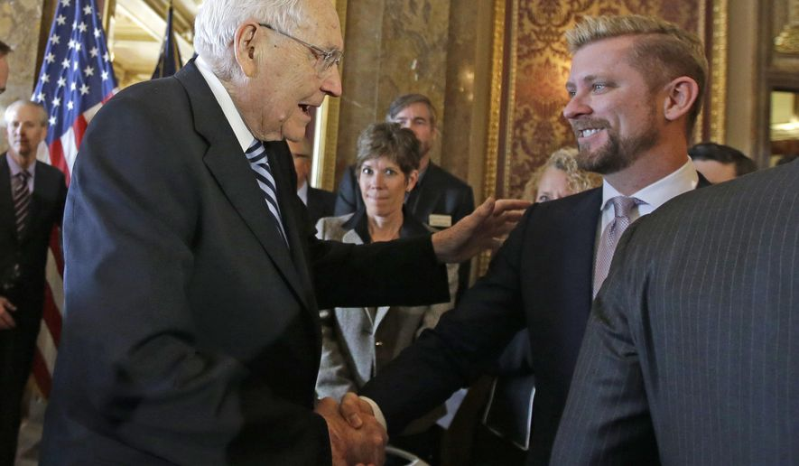 FILE - In this March 4, 2015, file photo, Elder L. Tom Perry, left, of the Church of Jesus Christ of Latter-day Saints Quorum of the Twelve Apostles shakes hands with Equality Utah executive director Troy Williams after Utah lawmakers introduced a landmark anti-discrimination bill during a news conference at the Utah State Capitol, in Salt Lake City. A Mormon church-backed antidiscrimination law that protects gay and transgender people and religious rights has taken effect amid skepticism from some LGBT residents. (AP Photo/Rick Bowmer, File)