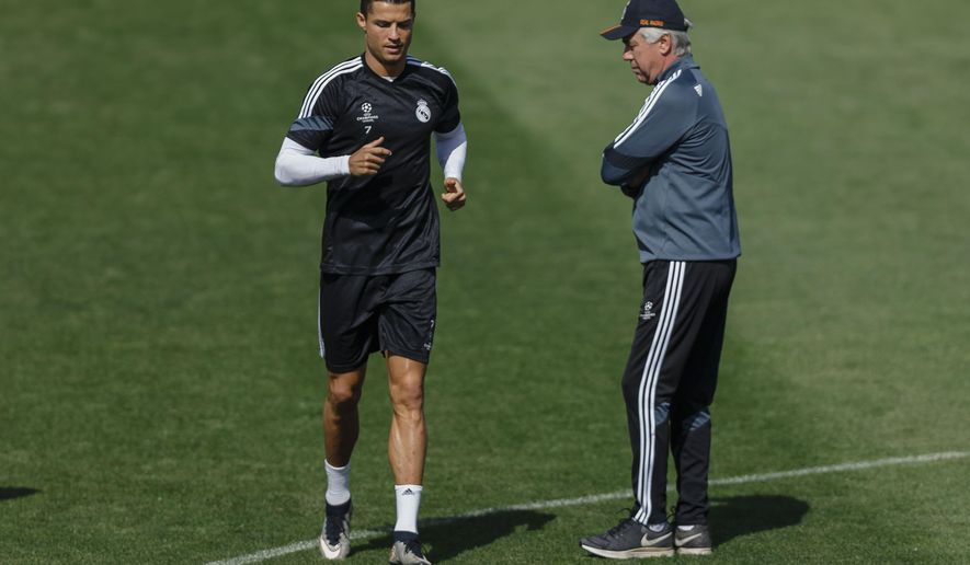 Real Madrid's Cristiano Ronaldo from Portugal, left, runs past head coach Carlo Ancelotti, from Italy, during a training session at the Valdebebas Stadium in Madrid, Spain, Tuesday, May 12, 2015 . Real Madrid will play against Juventus in a second leg semifinal Champions League soccer match on Wednesday. (AP Photo/Daniel Ochoa de Olza)