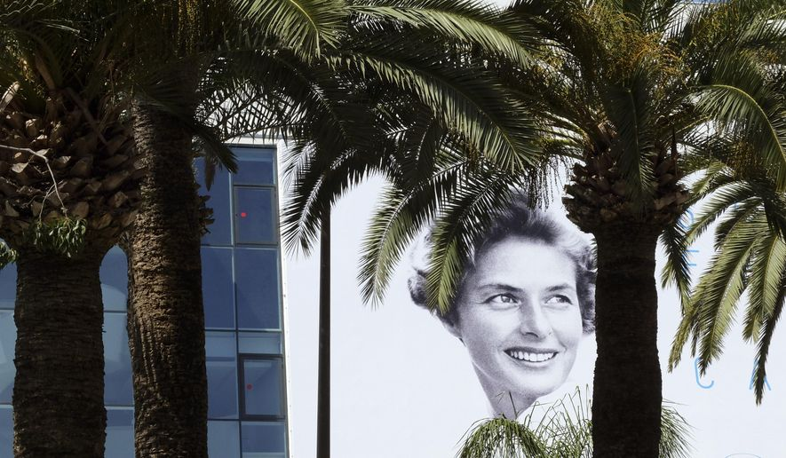 The official banner depicting actress Ingrid Bergman is seen between trees ahead of the 68th international film festival, Cannes, southern France, Tuesday, May 12, 2015. The festival opens on Thursday, May 13 and runs until Sunday, May 24. (AP Photo/Lionel Cironneau)