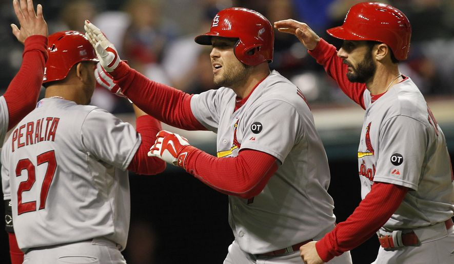 St. Louis Cardinals Matt Holiday, center, is congratulated by teammates Jhonny Peralta (27) and Matt Carpenter after hitting a solo home run during the eighth inning of a baseball game against the Cleveland Indians on Tuesday, May 12, 2015, in Cleveland. (AP Photo/Aaron Josefczyk)