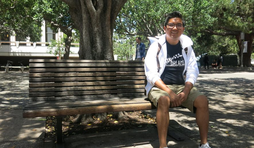 Rene Amel Peralta, 28, a chemistry student at University of California, Irvine, poses for a photo at the university, Tuesday, May 12, 2015. Peralta, who arrived in the U.S. at age 13 and only speaking Spanish, says he now uses more English than Spanish as he pursues his college degree. A report by Pew Research Center found a rising share of Hispanics in the United States speak proficient English while the percentage of those speaking Spanish at home has been declining.  (AP Photo/Amy Taxin)