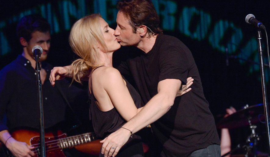 """David Duchovny and actress Gillian Anderson kiss during his performance at The Cutting Room, in support of the release of his debut album """"Hell Or Highwater"""", on Tuesday, May 12, 2015, in New York. (Photo by Evan Agostini/Invision/AP)"""