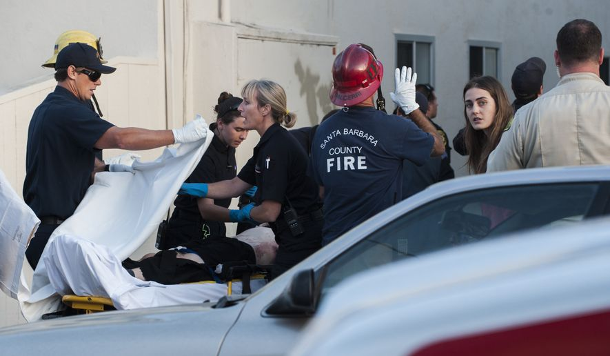 In this Monday, May 11, 2015, photo, paramedics cover a victim with a sheet in Isla Vista, near Santa Barbara, Calif. Two people were shot and a third was assaulted Monday night in an attack near the University of California, Santa Barbara in the same neighborhood where a man staged a killing rampage last year. (Kenneth Song/Santa Barbara News-Press via AP)