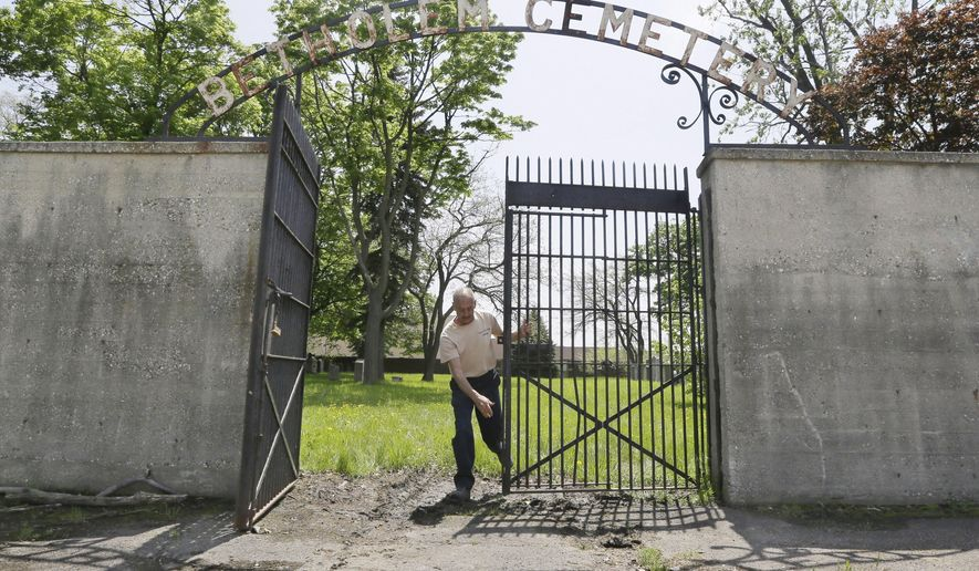 In a photo from Sunday, May 10, 2015, in Hamtramck, Mich., Gino Cardillo closes the gates of the Beth Olem Cemetery on the grounds of the General Motors Co.'s Detroit Hamtramck Plant. For plant security, public access is limited to a couple days a year, typically Sundays nearest to the Jewish holidays of Rosh Hashanah and Passover, and some special events. (AP Photo/Carlos Osorio)