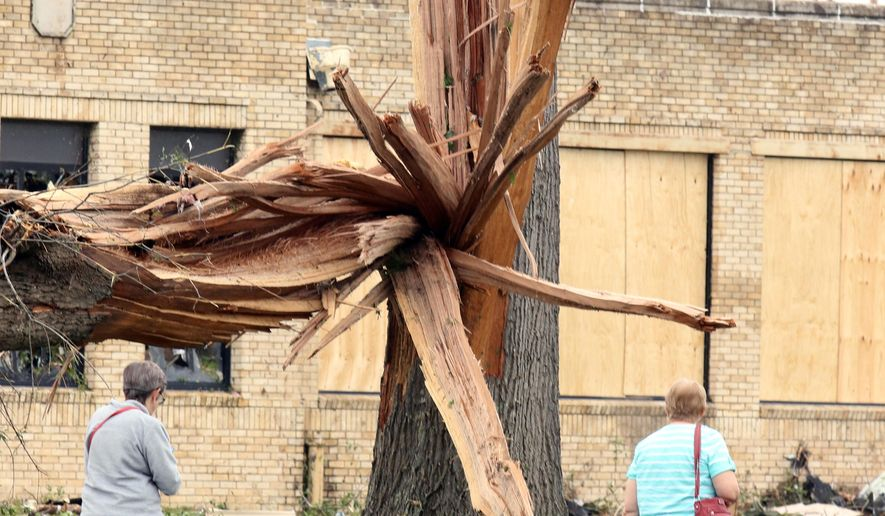 A lager tree is split down the center near the Van, Texas, intermediate and elementary schools campuses fter it was hit by severe weather, Monday, May 11, 2015. Emergency responders searched through splintered wreckage Monday after a line of tornadoes battered several small communities in Texas and Arkansas, killing at least five people. (AP Photos/Todd Yates)
